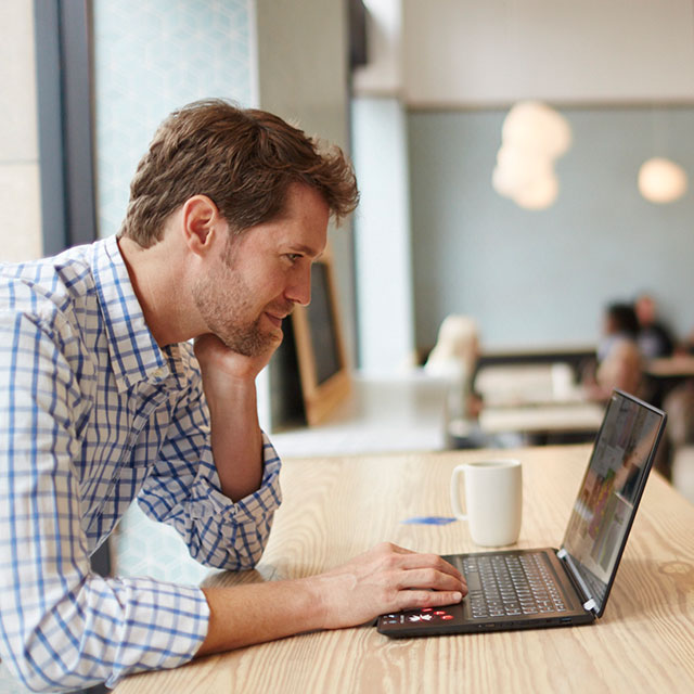 Man using laptop in cafe