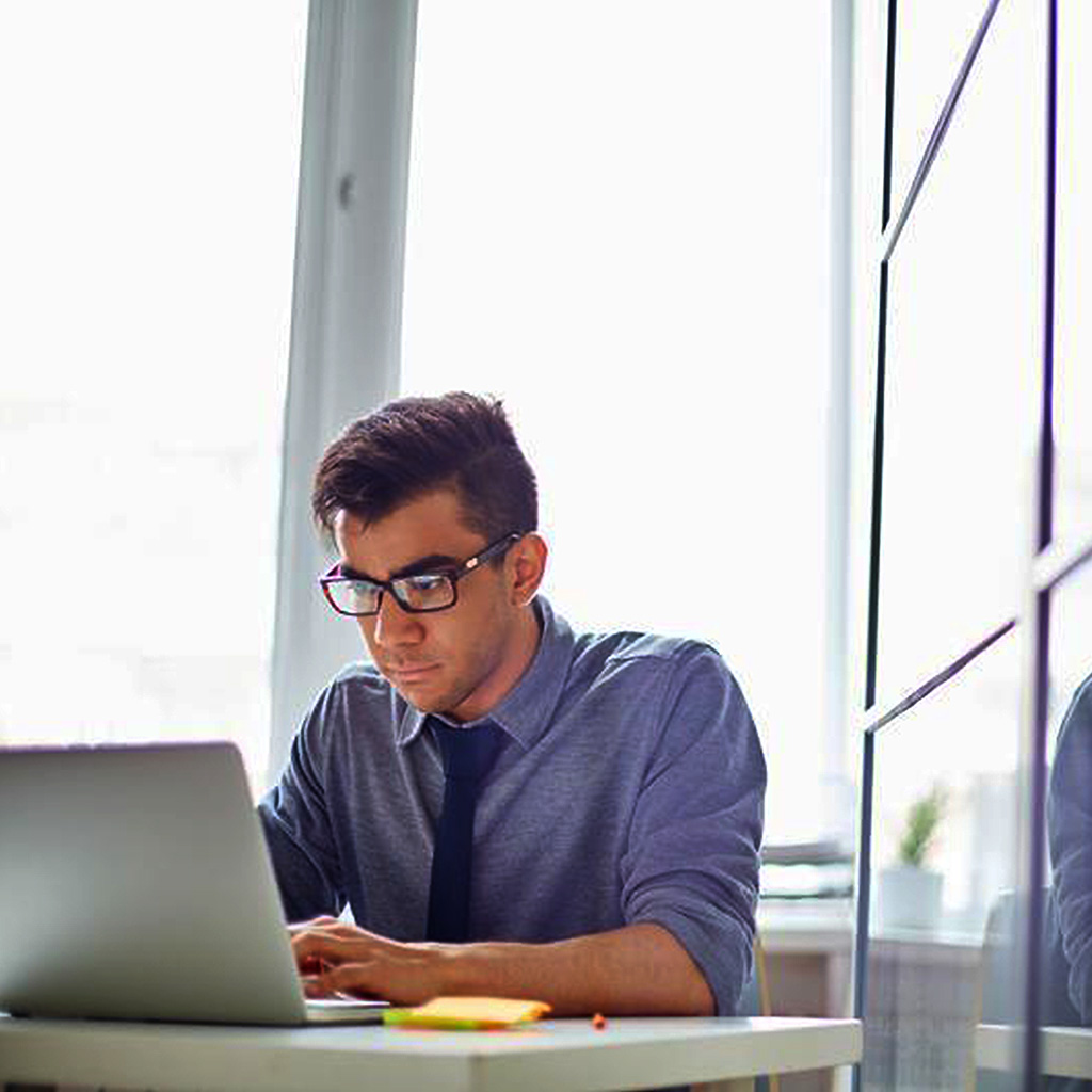 Man in a modern office on his laptop