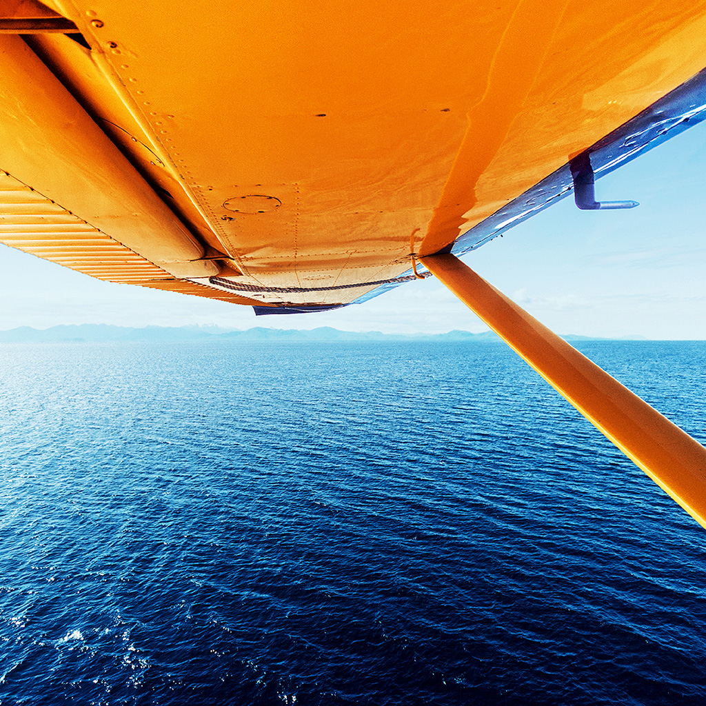 View of the underside of a plane's wing as it flies over water