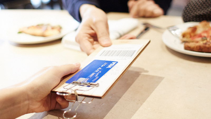 Hand holding a restaurant bill with a Visa credit card.