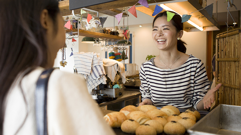 A smiling merchant bakery owner engaging with a customer.