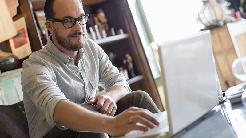 A man sitting while using a laptop.