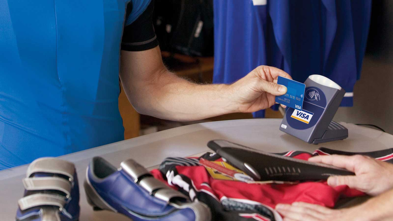 Person using Visa contactless card to pay for shoes.