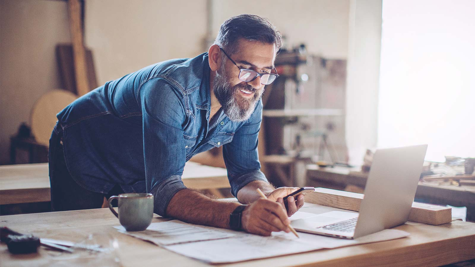 Smiling, casual man with beard, working with pencil, paper and laptop