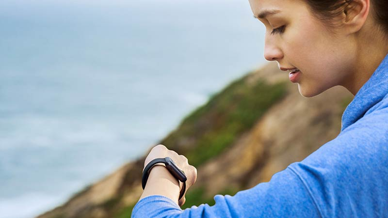 Woman checking her watch on top of a cliff overlooking the ocean.