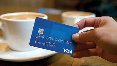 holding visa card in front of two cups of coffee
